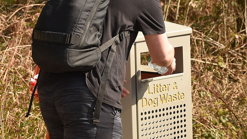 Image of A visitor places his rubbish in the bin at Balmaha car park.