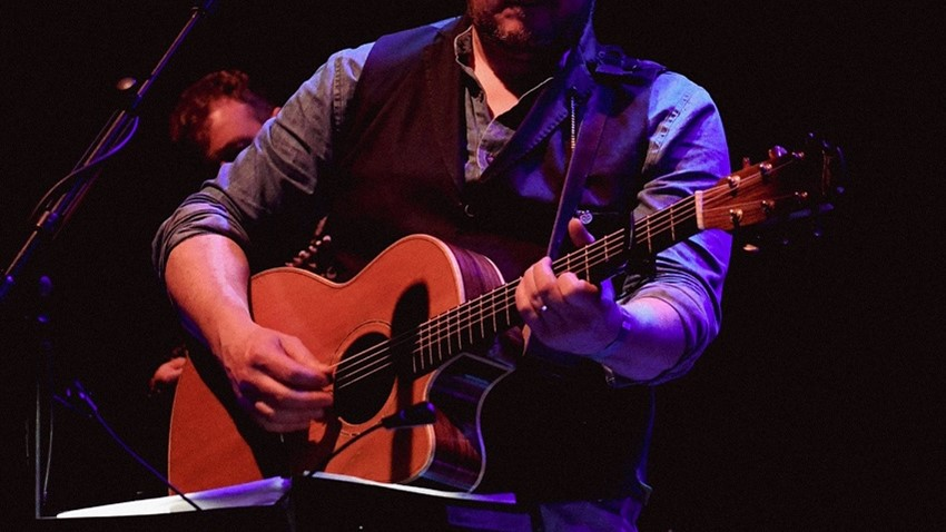 Image of A musician playing guitar at the Tolbooth