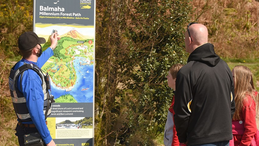 Image of A Council Community Enforcement Officer talks to members of the public at a visitor sign at Balmaha.