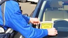 A parking ticket is placed on the windshield of a car parked outwith a bay at Balmaha.
