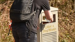 A visitor places his rubbish in the bin at Balmaha car park.