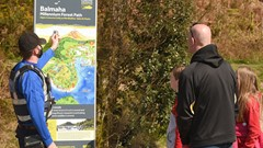 A Council Community Enforcement Officer talks to members of the public at a visitor sign at Balmaha.